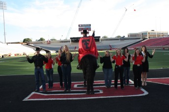 Charlie Snider, the Masked Rider with his field safety team (red) and several former Masked Riders that help him successfully appear at each game.